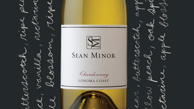 A bottle of the 2018 Sean Minor Sonoma Coast Chardonnay surrounded with cursive decorative text.