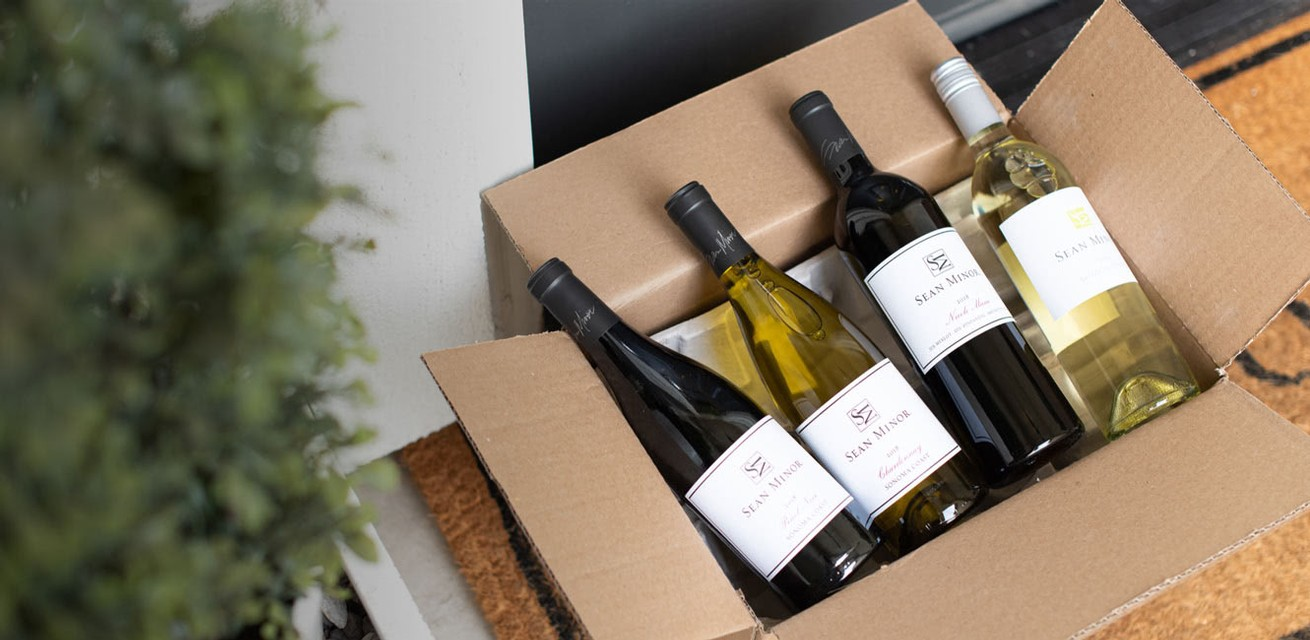 A shipping box on a doorstep with four bottles of Sean Minor Wines